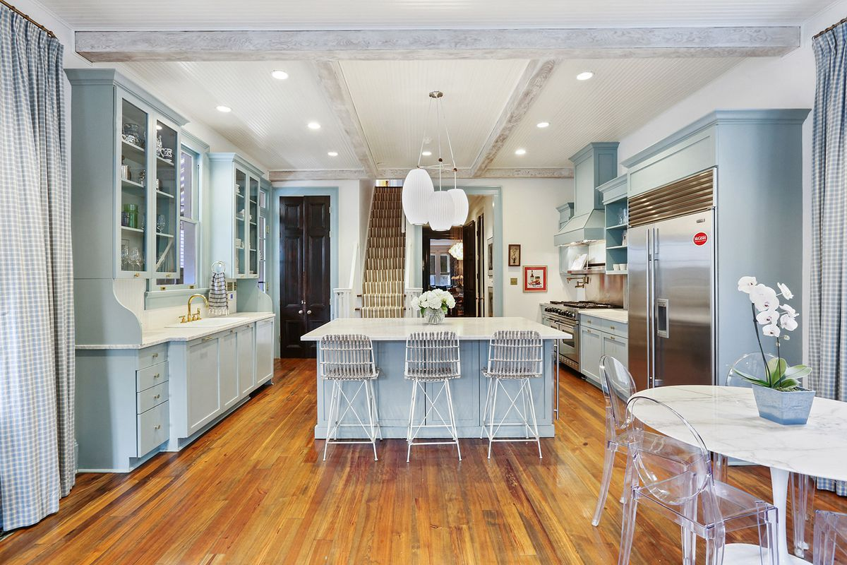 A kitchen with pale blue, glass front cabinets and a marble-topped island