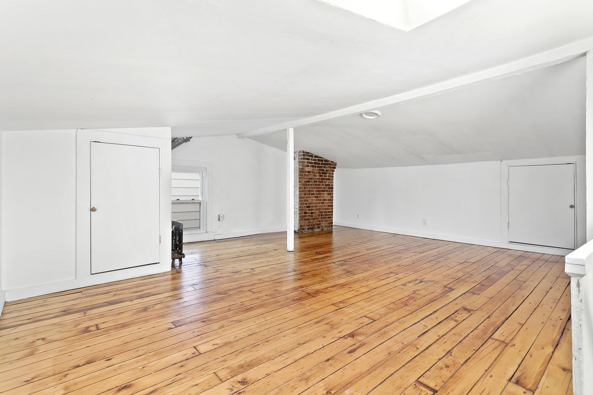An attic with hardwood floors, white walls, exposed brick, and a small window.