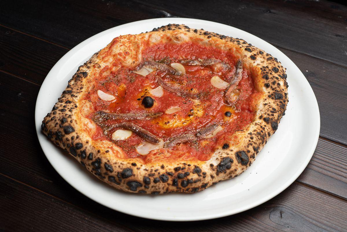 Marinara pizza with anchovies on a white plate at Ronan