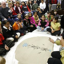 Julius Chavez tells a story with sand painting. Academic indicators in Nebo and San Juan Districts rose after language and culture classes began.