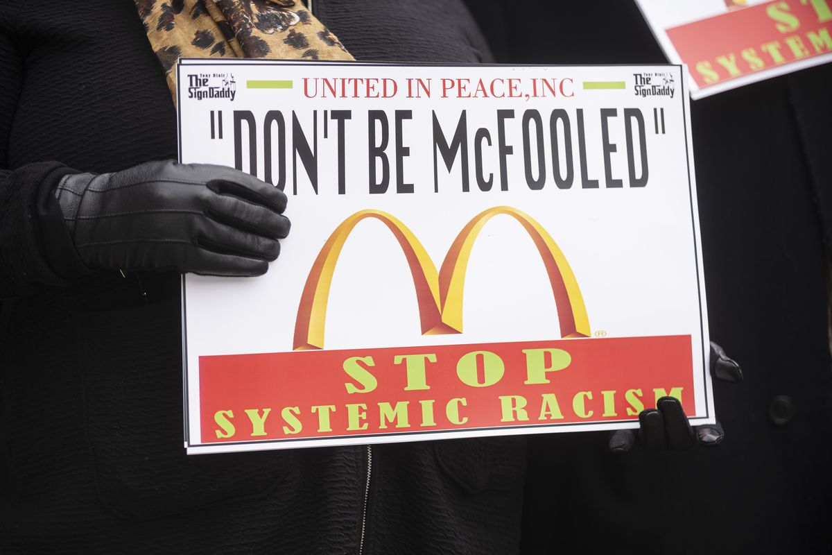 A protester holds a sign outside McDonald's global headquarters in the West Loop on Monday, Feb. 22, 2021.