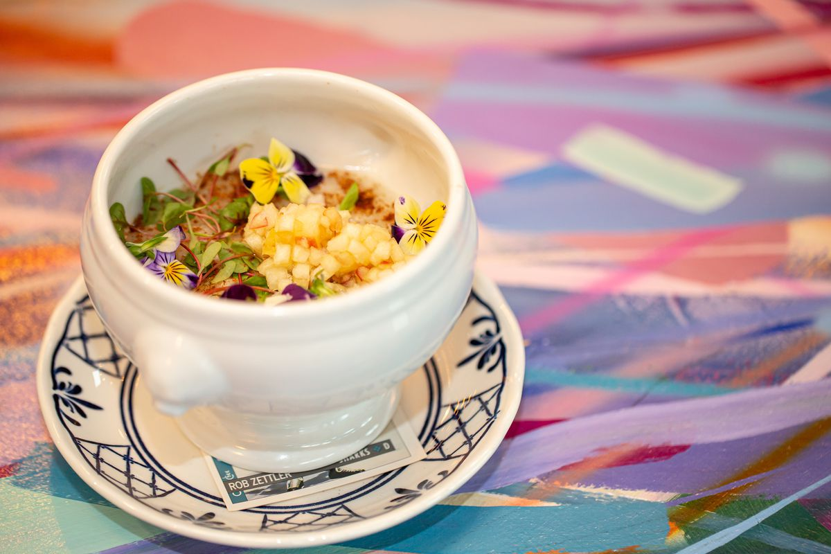 A shot of the gold rice pudding topped with violets in white dish on the multi-colored striped bar