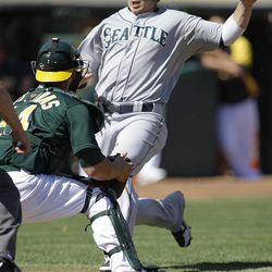 Oakland Athletics catcher George Kottaras, left, waits to tag out Seattle Mariners' Justin Smoak at home plate in the second inning of a baseball game Sunday, Sept. 30, 2012, in Oakland, Calif. Smoak attempted to score on a single by Carlos Triunfel.