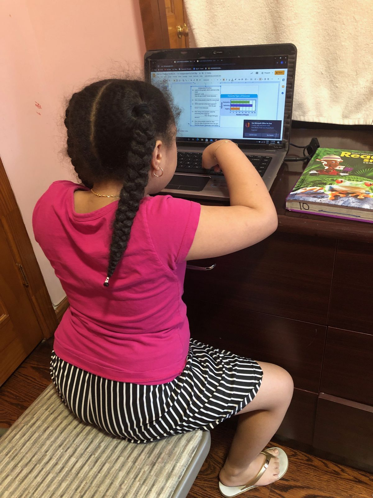Alhia, 8, is enrolled at P.S. 330 in Corona, Queens. She learns from a laptop propped on her dresser in her bedroom.