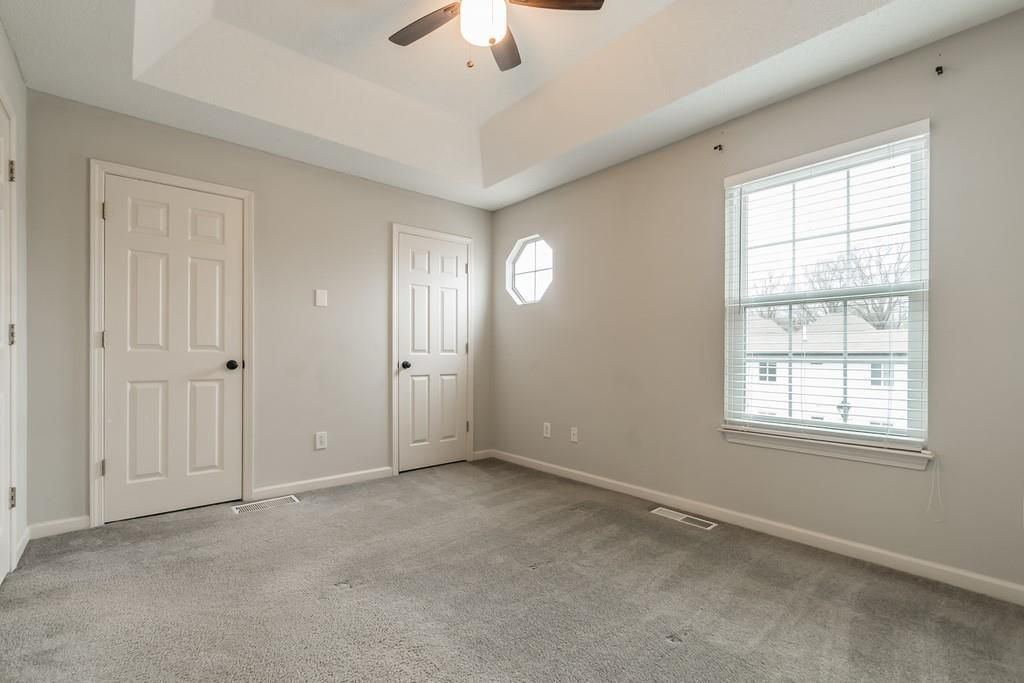 Empty bedroom with gray carpet, window, and tray ceiling with ceiling fan.
