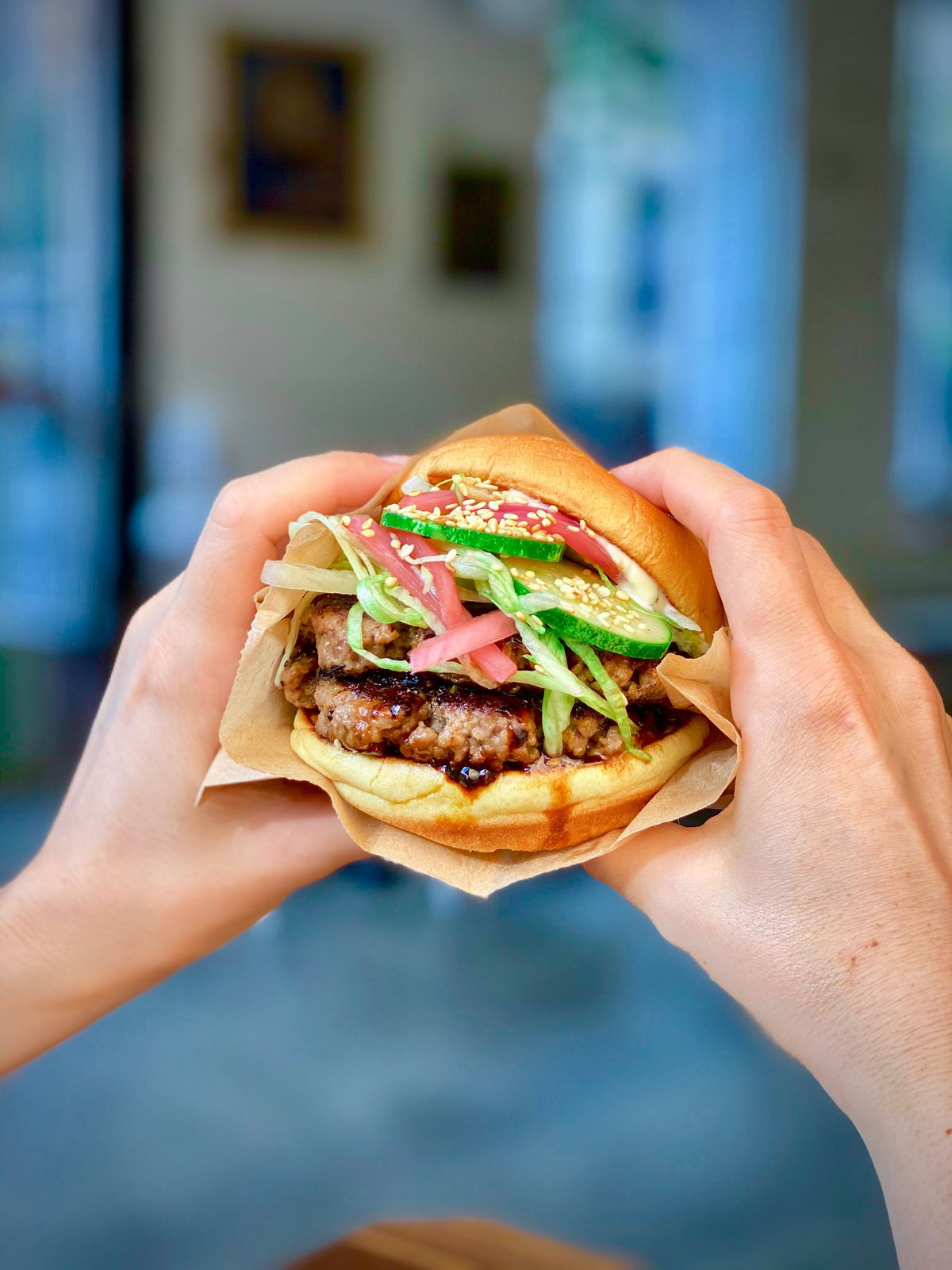 Two white hands hold a burger overflowing with patties, cucumber, pickled onions, greens, and sesame seeds