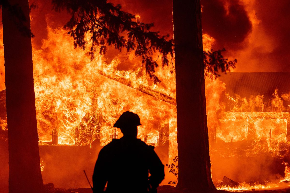 A firefighter is silhouetted by flames and a burning building