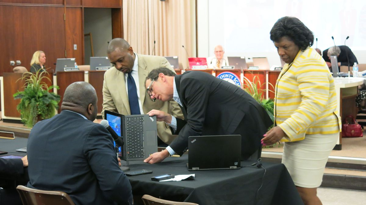 Shelby County board members examine devices at Tuesday meeting.