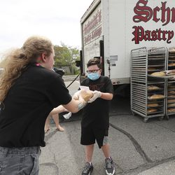 Schmidt's Pastry Cottage volunteer James Bowen hands out two loaves of bread to Willow Isbell at Cyprus High School in Magna during a Free Bread Project giveaway on Sunday, May 17, 2020.