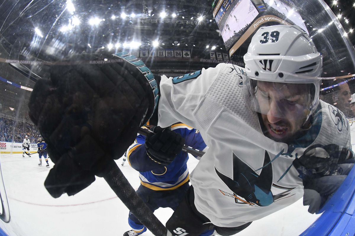 May 15, 2019; St. Louis, MO, USA; San Jose Sharks center Logan Couture is checked by St. Louis Blues center Oskar Sundqvist during the third period in game 3 of the Western Conference Final of the 2019 Stanley Cup Playoffs at Enterprise Center.
