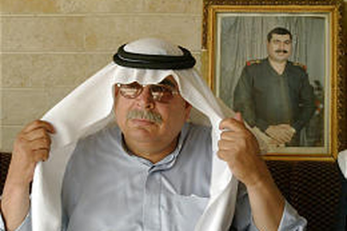 Abdullah Hashim Ahmad poses in front of picture of Sultan Hashim Ahmad, his brother.