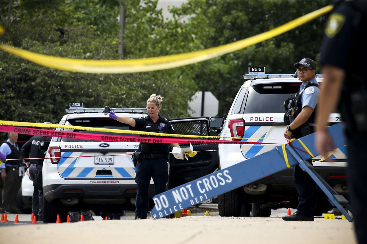 """Police vehicles and officers seen behind lines of caution tape and a """"do not cross"""" barricade."""
