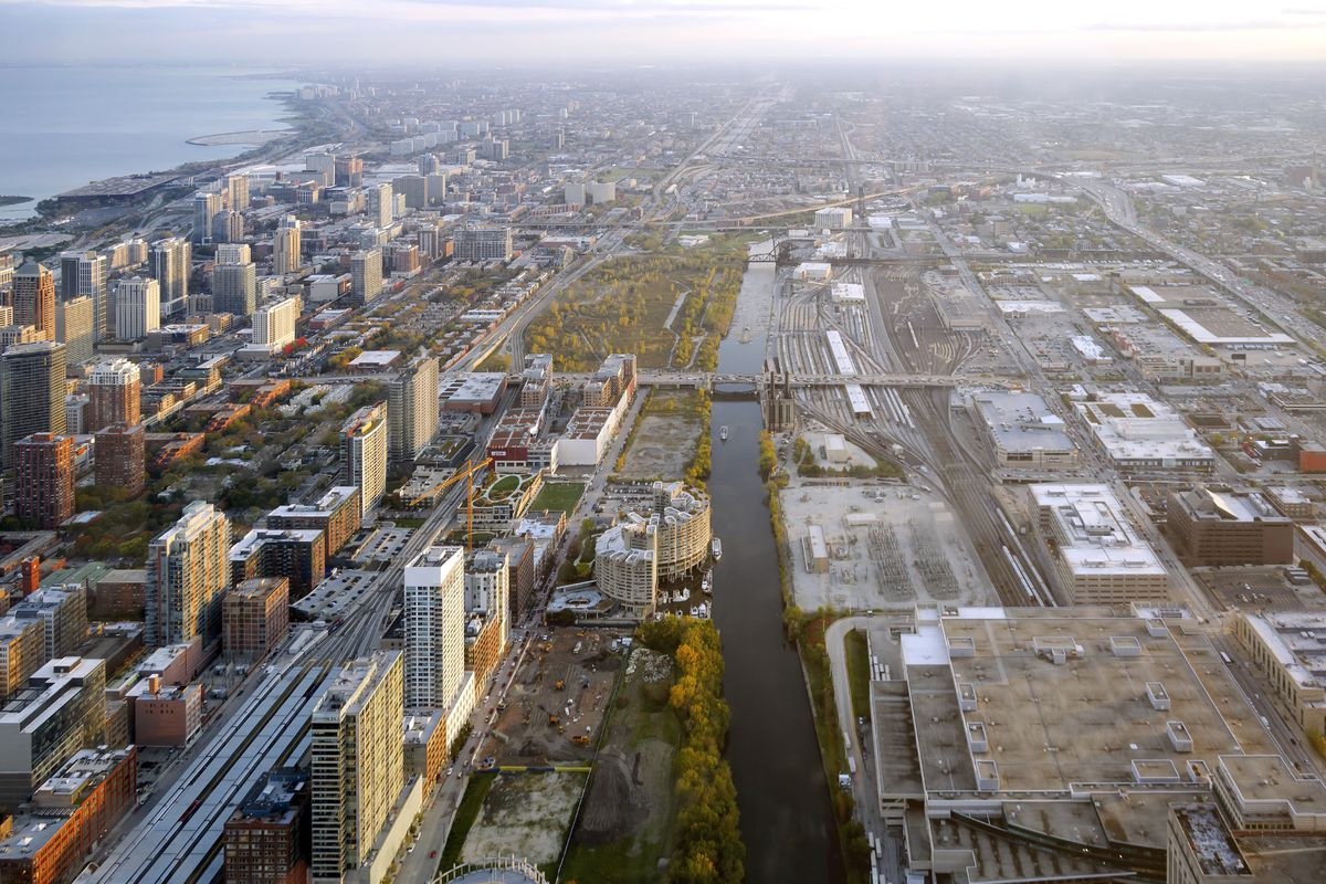A bird's eye view of Chicago. There is a river, a part of the lake, green space, and a collection of tall towers.