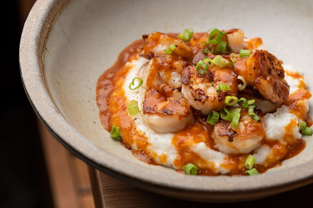 A plate of shrimp and grits in light orange cayenne sauce.