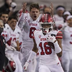 Utah safety Zemaiah Vaughn (16) runs 73 yards as quarterback Jake Bentley (8) and head coach Kyle Whittingham, left, react on the sideline after Vaughn intercepted a pass against Washington during the first half of an NCAA college football game, Saturday, Nov. 28, 2020, in Seattle.