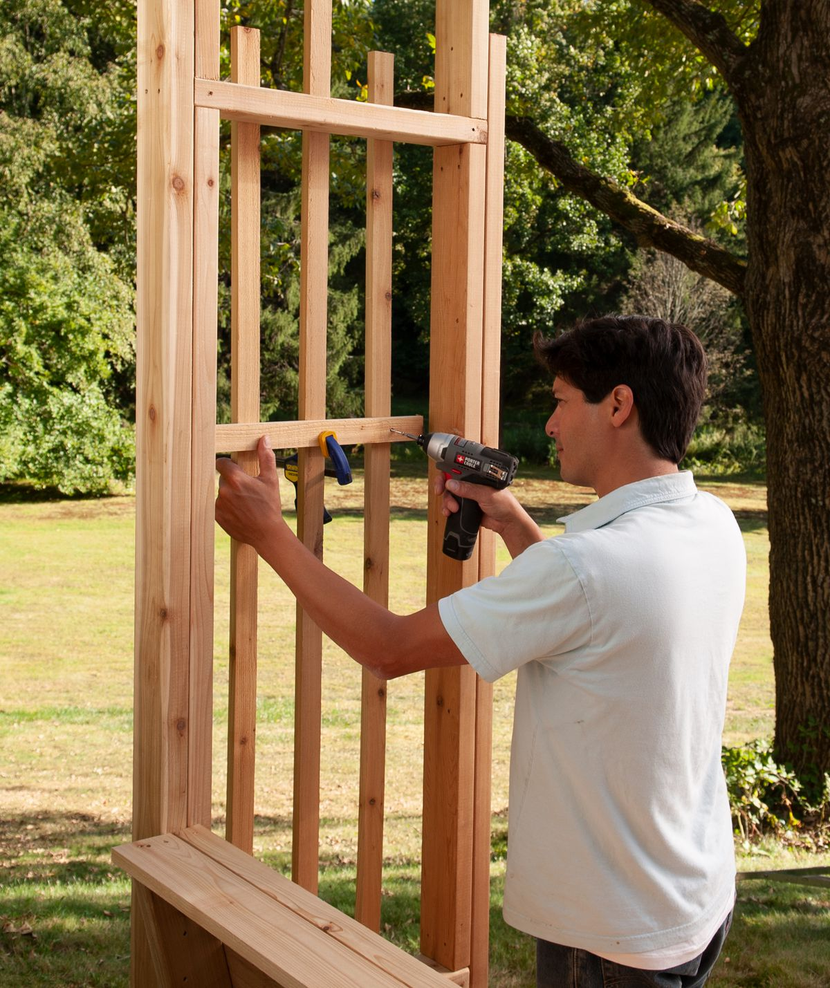 Man Cuts And Installs Horizontal Wood Strips Of Arbor Bench