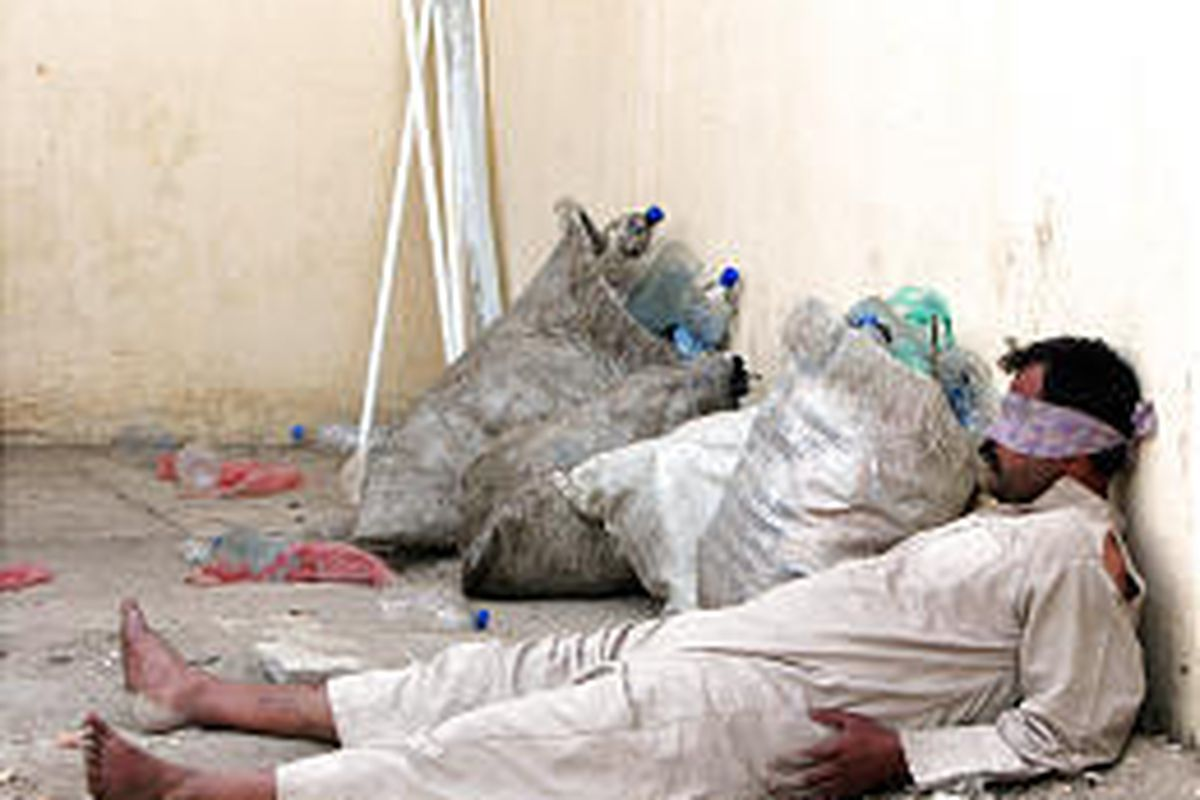 A blindfolded detainee, suspected of being an insurgent, lies at the Iraqi Wolf Brigade headquarters in Baghdad. The Interior Ministry said 115 suspects were arrested.
