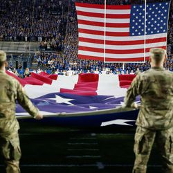 U.S military members hold the American flag as BYU and Utah prepare to compete in an NCAA college football game at LaVell Edwards Stadium in Provo on Saturday, Sept. 11, 2021.
