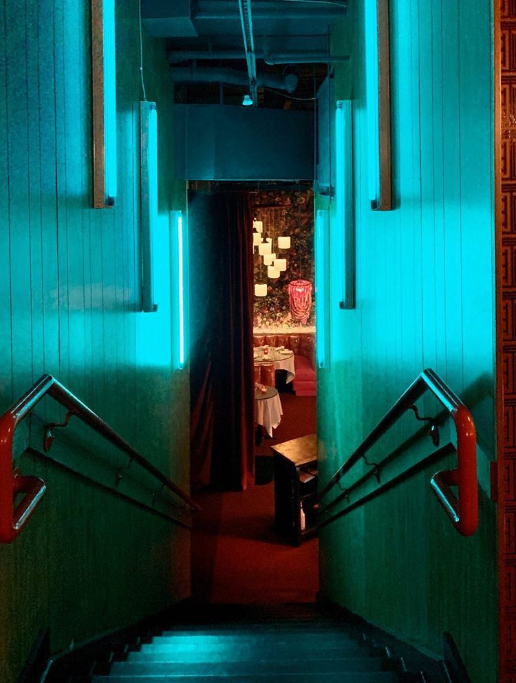 A turquoise lit stairwell leading down into the dining room at Ruby Chow's in Atlanta
