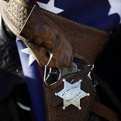 A revolver rests in its holster with a flag on a saddle at a dedication of a headstone for deputy James D. Hulsey, who was killed in the line of duty in 1913. The Salt Lake County Sheriff's Office held the ceremony Monday in the Bingham City Cemetery.