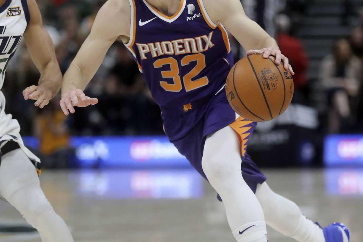 Phoenix Suns guard Jimmer Fredette (32) dribbles around Utah Jazz guard Raul Neto (25) during an NBA basketball game at the Vivint Smart Home Arena in Salt Lake City on Monday, March 25, 2019. The Jazz won 125-92.