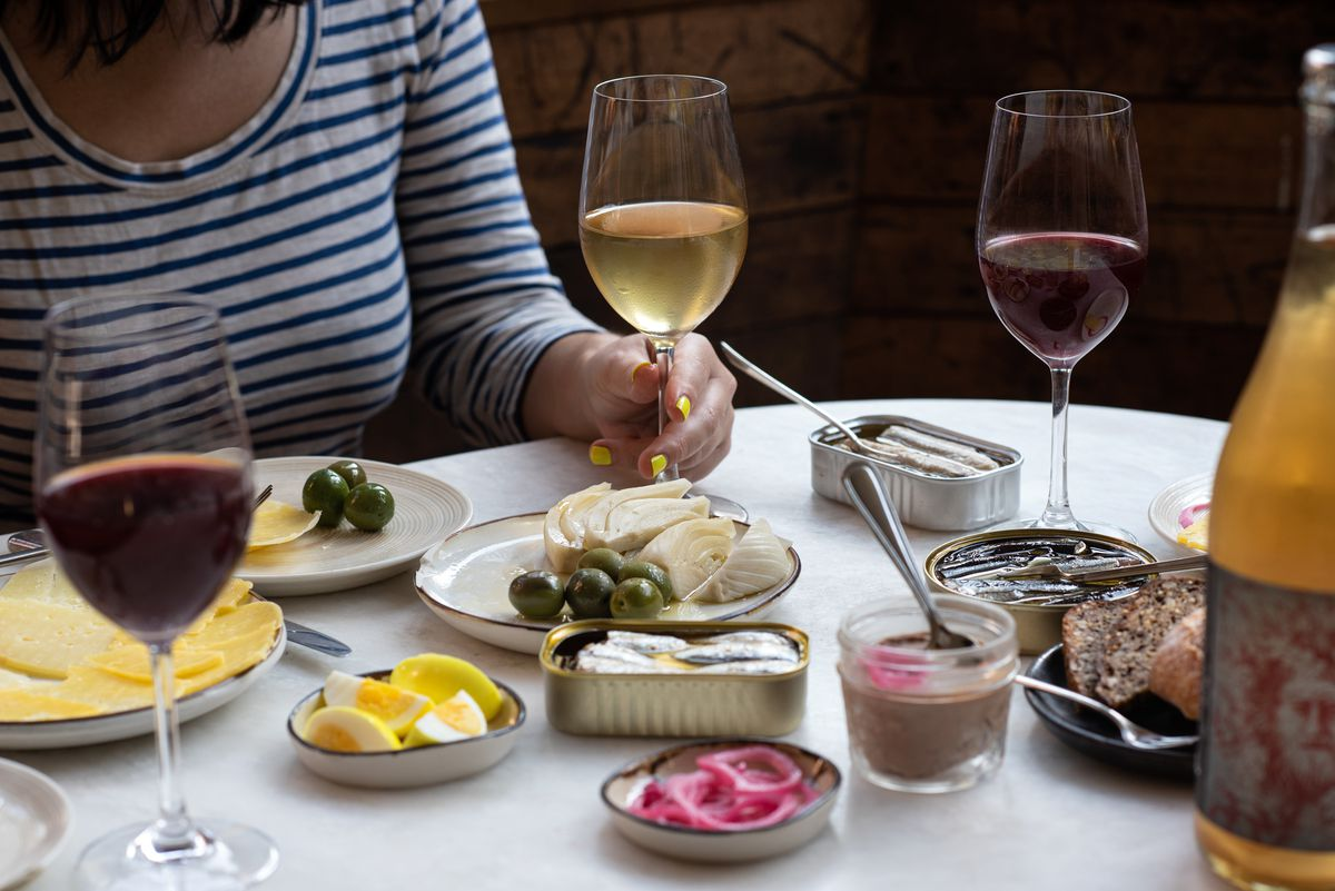 A woman sits at a table, holding a glass of white wine. On the table, there are various small-plate appetizers including artichokes, olives, pickled onions, and hardboiled eggs.