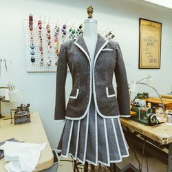 Thom Browne's costume includes a felt blazer and pleated skirt.