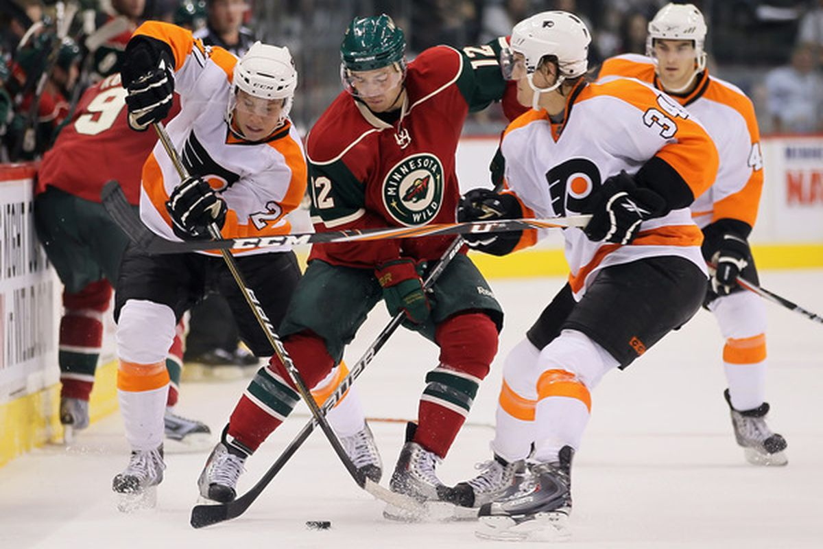 ST PAUL MN - SEPTEMBER 25:  Erik Gustafsson #27 and Ben Holmstrom #34 battle for the puck as Eric Wellwood looks on. Those three have been bright spots in the dark, dark world of the Phantoms.  (Photo by Jeff Gross/Getty Images)