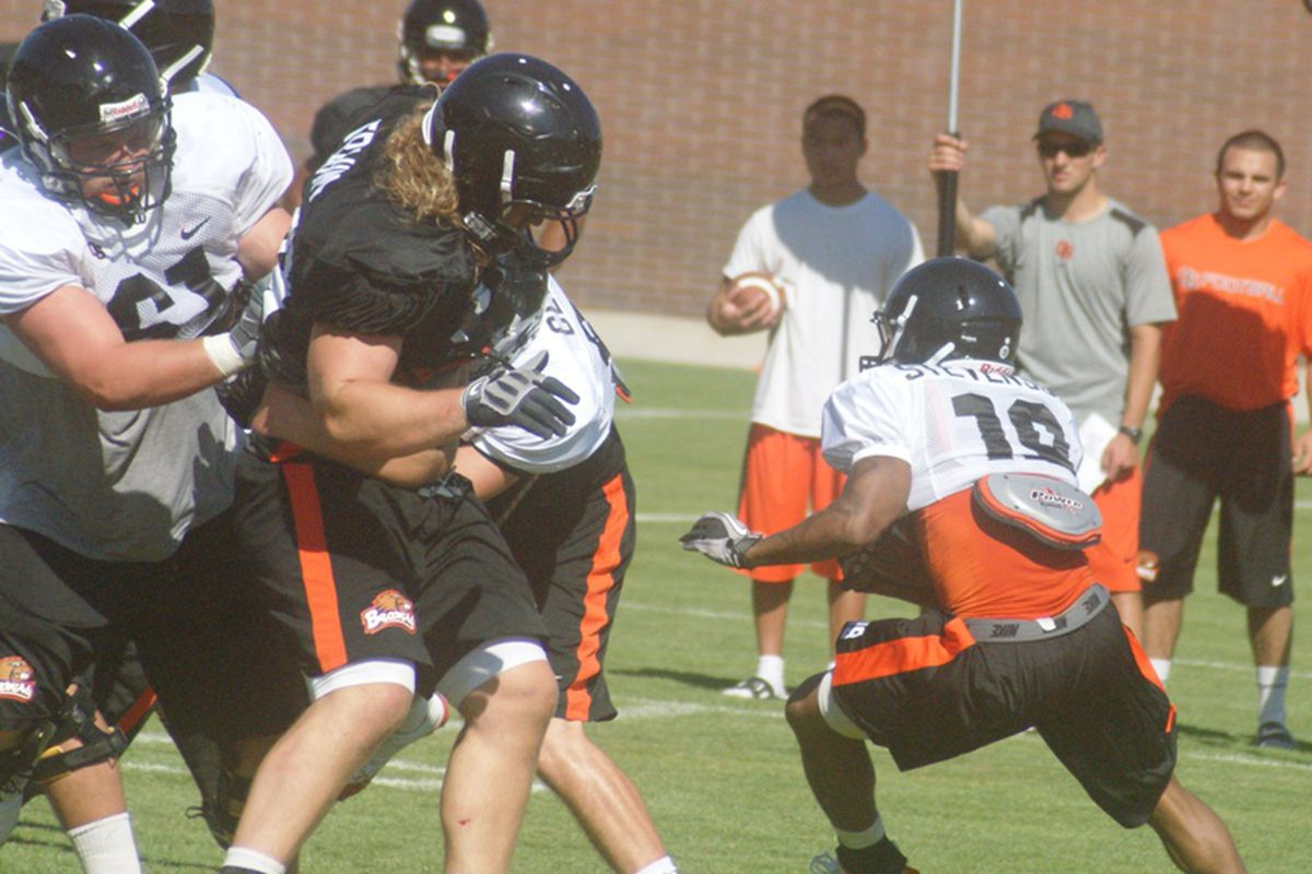 Jovan Stevenson cuts past a rushing Kevin Frahm as Oregon St. increased the level of contact in day 3 of fall practice.  <em>(Photo by Andy Wooldridge)</em>