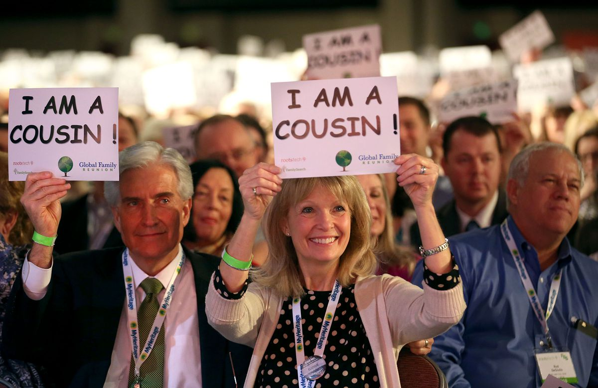 """Larry Beardall and Laurie Beardall hold up """"I am a cousin"""" signs during A.J. Jacobs' keynote speech at RootsTech at the Salt Palace in Salt Lake City on Saturday, Feb. 14, 2015. This year's virtual-only conference helped more than one million participants to connect with relatives."""