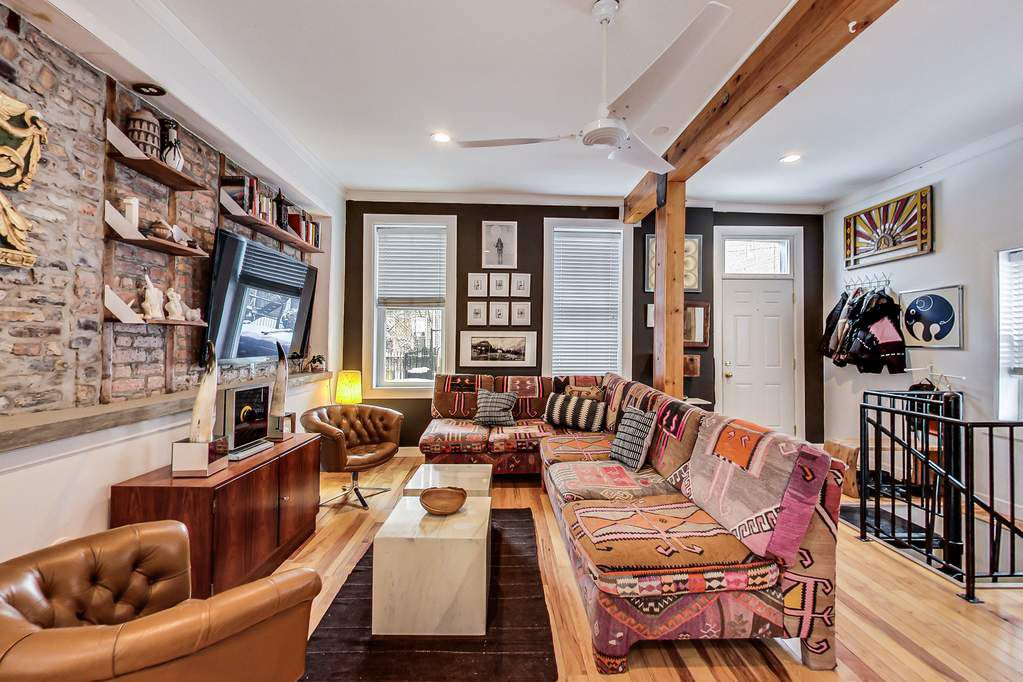 A living room with wooden beams, a large sectional couch, a tv, exposed brick, and leather chairs.
