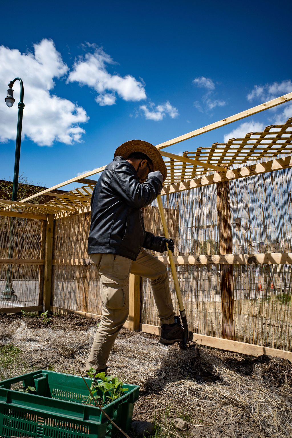 Man wearing hat digging into soil by a fence.