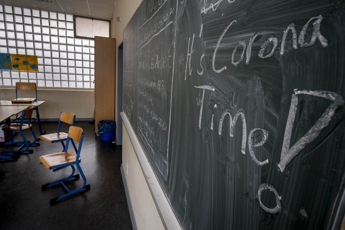 In this Friday, March 13, 2020 file photo the slogan 'It's Corona Time' is written on the chalkboard of an empty classroom of a high school in Frankfurt, Germany.
