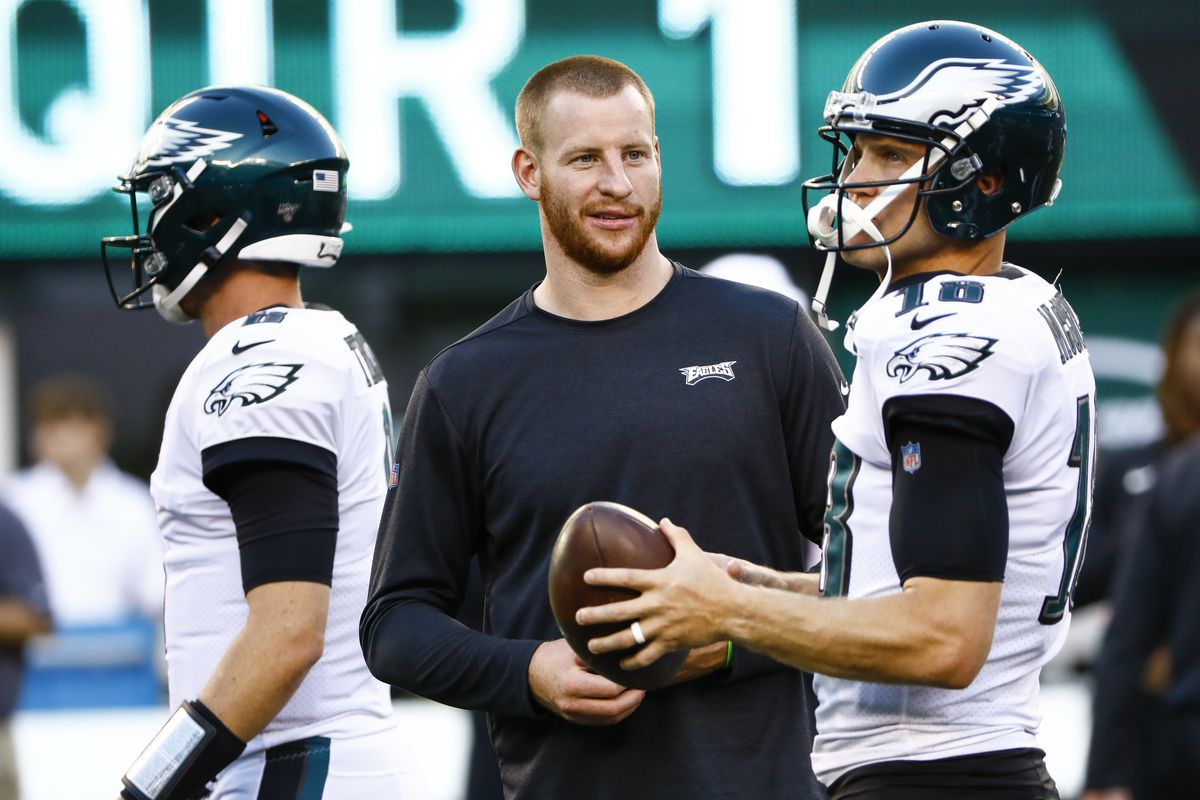 Philadelphia Eagles quarterback Carson Wentz talks with Philadelphia Eagles quarterback Josh McCown prior to a preseason game against the New York Jets at MetLife Stadium on August 29, 2019 in East Rutherford, New Jersey.