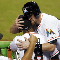 Miami Marlins' John Buck, right, hugs bench coach Joey Cora as pitching coach Randy St. Claire, left, cheers after Buck scored on a single by Gorkys Hernandez during the third inning of a baseball game against the Atlanta Braves, Tuesday, Sept. 18, 2012, in Miami.