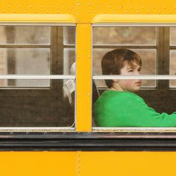 A Fremont High School student waits on the bus as students are evacuated from the school after reports of a student with a gun were made in Ogden Monday, Dec. 1, 2014.