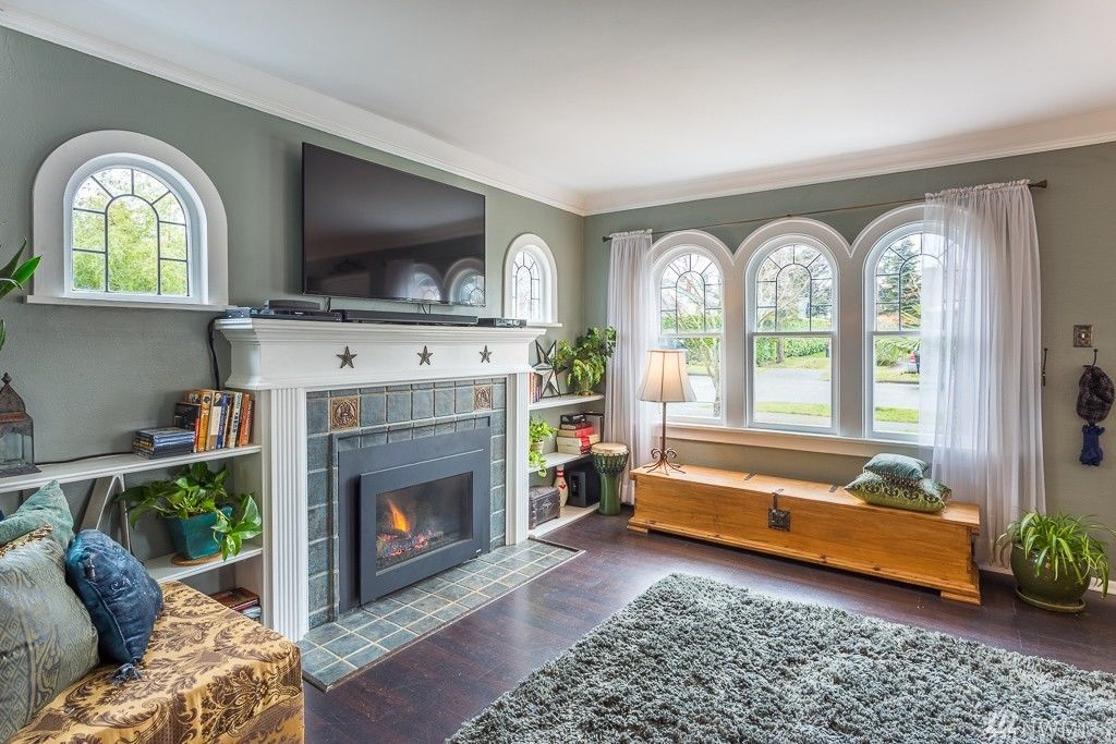 A fireplace in a Spanish Revival living room with arched windows. A TV is above the fireplace.