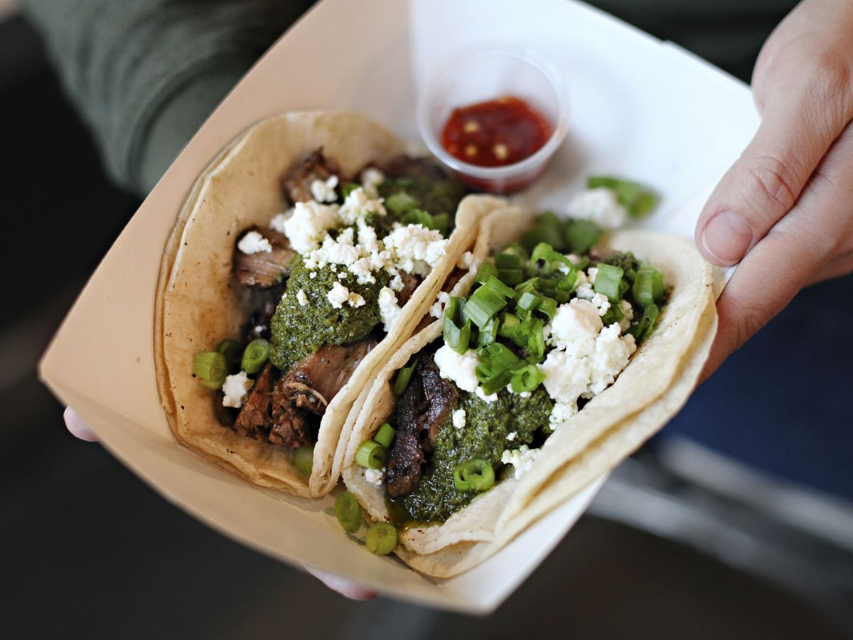 A hand holds a paper boat of two tacos topped with green sauce