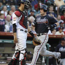 Atlanta Braves' Matt Diaz, right, crosses the plate beside Houston Astros catcher Jason Castro in the second inning of a baseball game Monday, April 9, 2012, in Houston.