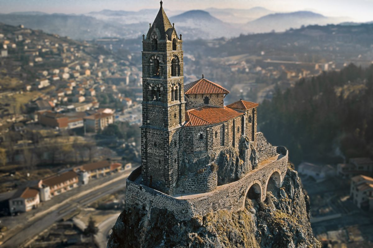 """The exterior of <span data-author=""""843"""">Saint-Michel d'Aiguilhe chapel in France. The church is situated on a tall cliff which is a volcanic needle. The roof is red and the facade is stone.</span>"""