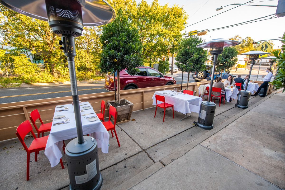 An outdoor seating area on the street along the sidewalk curb with white tablecloth tables, red chairs, heating lamps, and a wooden fence