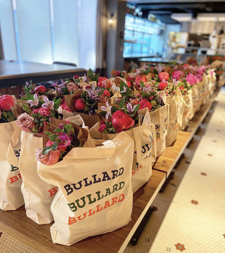 """A long wooden table carries a dozen or two totes bags. Each reads """"Bullard"""" three times, and is filled with a bouquet of flowers."""