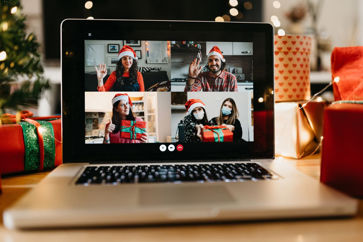 Video call of a laptop screen showing five people dressed in holiday wear.