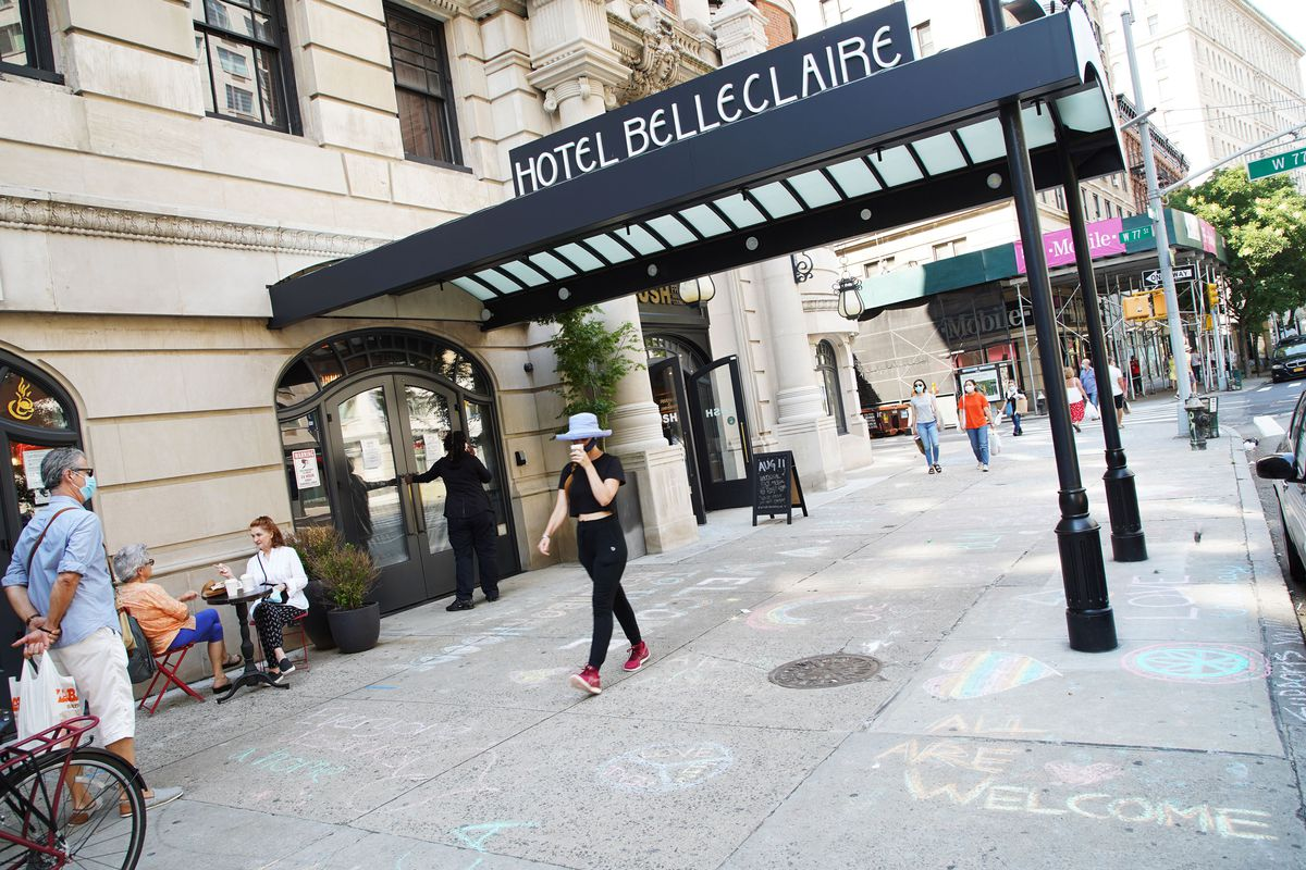 """All are welcome"""" is written in chalk on the pavement below a decorative awning that reads Hotel Belleclaire on an ornate, limestone building on a street in the Upper West Side of Manhattan. The New York City mayor is housing the homeless in these hotels."""