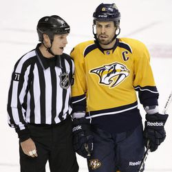 In this April 11, 2012 photo, linesman Brad Kovachik (71) talks to Nashville Predators defenseman Shea Weber (6) after time expired in the Predators 3-2 win over the Detroit Red Wings in Game 1 of a first-round NHL hockey playoff series in Nashville, Tenn. Speculation is heavy that Weber may be punished by the NHL for retaliating against Red Wings' Henrik Zetterberg after the final horn.