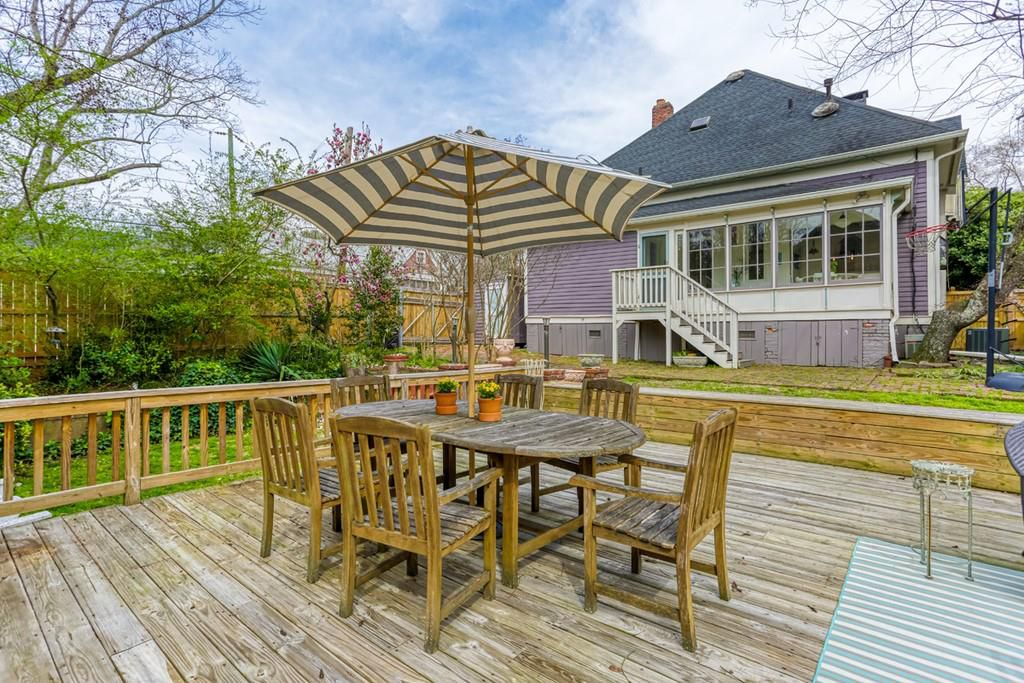 A backyard deck with a basketball goal at right.