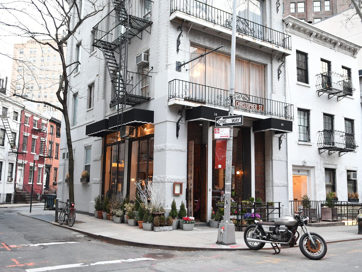 A West Village street with a motorbike. The building on the corner has a light grey facade.