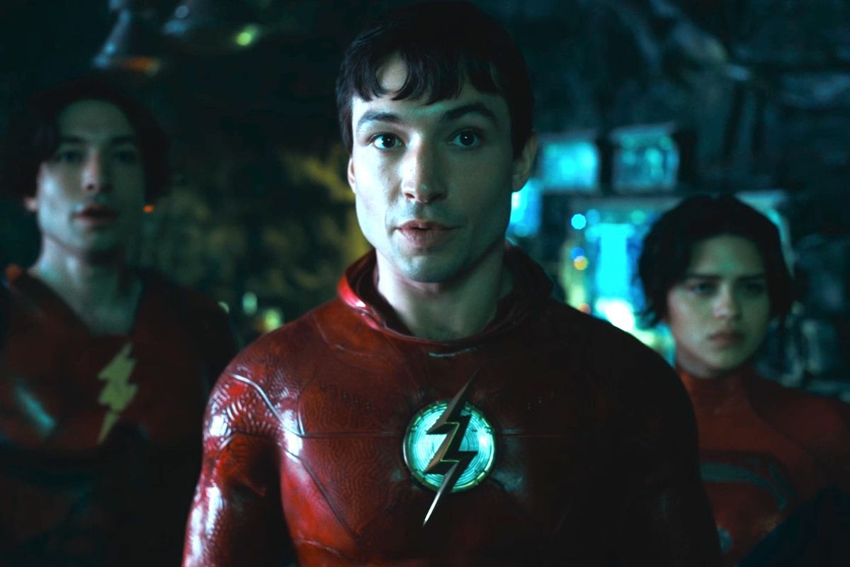 Ezra Miller as The Flash of two dimensions and the new Supergirl Sasha Calle stand in the batcave