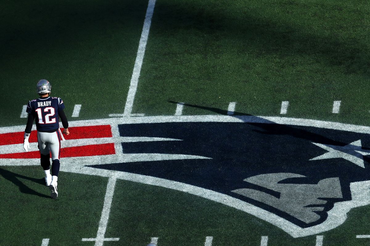 Tom Brady #12 of the New England Patriots walks to the bench over the Patriots logo during the game against the Miami Dolphins at Gillette Stadium on December 29, 2019 in Foxborough, Massachusetts.