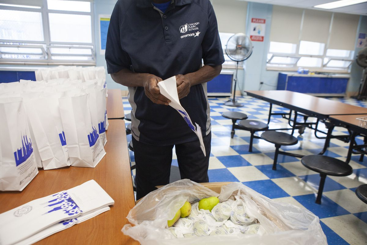 A food service worker assembles lunch bags.